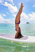 Hawaii, Beautiful Brunette Girl Doing A Headstand On Her Stand Up Paddle Board