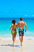 Hawaii, Oahu, Lanikai, Young Couple Running Into The Ocean.