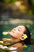 Hawaii, Oahu, Closeup Of Young Woman's Face Relaxing In Tropical Pool.
