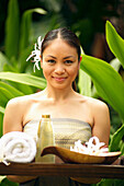 Beautiful Polynesian Woman At A Spa Holding A Tray Of Spa Implements.