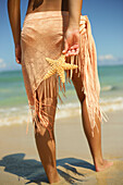 Girl Standing On Tropical Beach Wearing Pareo, Holding A Starfish, Legs And Torso
