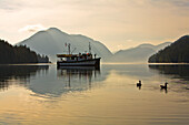 Adventure Boat On James Bay Silhouetted Against The Don Peninsula, Great Bear Rainforest, British Columbia