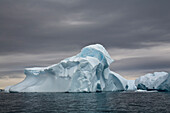 Gigantic Icebergs Adrift In Waddington Bay Against A Cloudy Sky, Antarctica