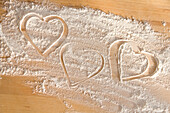 Hearts Drawn In Flour On Wooden Table Top