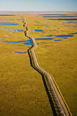 Aerial View Of Oil Gathering Lines Alongside A Dirt Road At Prudhoe Bay's Kuparuk Field In Alaska