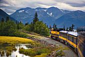 View Of An Alaska Railroad Train Travelling Between Anchorage And Seward Along Turnagain Arm In Southcentral Alaska, Summer