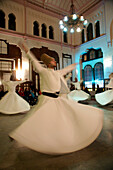 Performance By Whirling Dervishes Of The Galata Mevlevi Lodge At Sirkeci Station Waiting Room, Sultanahmet, Istanbul, Turkey. (C) Marc Jackson/Axiom