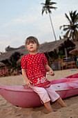 Kiki Lett aged 5 sits on a canoe, Patnum Beach, Goa, India.