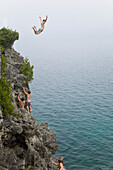 'Man leaping from a cliff into turquoise water of Georgian Bay in Bruce Peninsula National Park; Ontario, Canada'