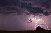 'Lightning strikes over the prairies as it approaches an old abandoned farm house; Val Marie, Saskatchewan, Canada'