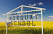 'School sign in front of bloom stage canola field near Somerset; Manitoba, Canada'