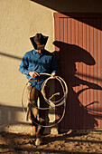 Agriculture - Cowboy with a lasso rope standing against a barn in evening light / Childress, Texas, USA.