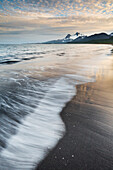'Landscape of waves washing up along the sandy beach of Katmai National Park; Alaska, United States of America'