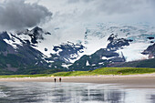 'Hikers walk along the sandy beach on the coast of Katmai National Park, Alaska Peninsula; Alaska, United States of America'