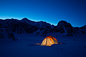 'Mountain tent on Ruth Glacier in evening, illuminated by head lamp with the summit of Mt. McKinley in background, Denali National Park and Preserve; Alaska, United States of America'