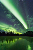 'Green bands of northern lights, aurora borealis, over a frozen lake, Brooks range; Alaska, United States of America'