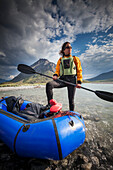Female paddler with her paddle and pack raft, Marsh Fork of the Canning river in the Arctic National Wildlife Refuge, Brooks range mountains, Alaska.