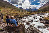 Couple relax next to Arrigetch creek with Xanadu, Elephant's Tooth and Parabala mountains in the distance, Arrigetch Peaks, Gates of the Arctic National park, Alaska.