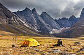 Backpacker enjoys a campsite on the autumn tundra with a view of East and West Maiden and Camel peaks in the distance, Arrigetch Peaks, Gates of the Arctic National Park, Alaska.