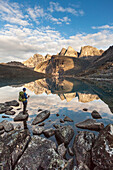 Hiker views East and West Maiden and Camel peaks as they reflect in a mountain lake in the Arrigetch Peaks, Gates of the Arctic National Park, Alaska.