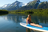 Woman of Korean ethnicity doing yoga and yoga stretches on a stand up paddle board, Moose Ponds in Portage Valley, Chugach National Forest, Southcentral Alaska