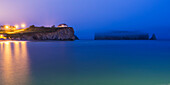 'Perce Rock and the town of Perce on the Gaspe Peninsula at nighttime; Perce, Quebec, Canada'