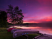 'Sunrise explodes over Echo Lake in Aroostook State Park with canoes on the shore; Presque Isle, Maine, United States of America'