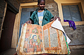 'Young boy showing an ancient bible at a church; Ethiopia'