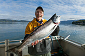 60 year old male sport fisherman holds King (Chinook) salmon on back of fishing boat in Kachemak Bay near Homer, Kenai Penninsula, Alaska, Autumn.