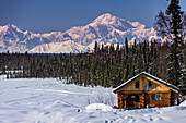 Log cabin with Mt. Mckinley and Alaska Range in the background, Southcentral, Alaska