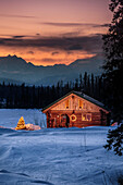 Log cabin with Christmas tree and decorations, Mt. Mckinley and Alaska Range in the background. Southcentral, Alaska