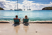 'Tourists sit at the water's edge on a beach in the Virgin Islands; United States of America'
