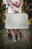 'A couple holding a vintage suitcase; Edmonton, Alberta, Canada'