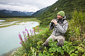 Swiss biologist and photographer glassing while sitting on a cliff overlooking Katmai Coast, Kukak Bay, Southwest Alaska