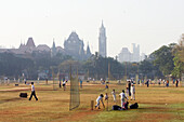 'Early morning games of cricket and in the nets at Cross Maiden with Law Courts in background; Mumbai, Maharashtra State, India'