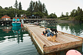 Couple relax on the dock in front of the Saltry restaurant along with two dogs, Halibut Cove, Southcentral Alaska