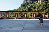 'A nun standing outside the Benedictine Abbey; Montserrat, Catalonia, Spain'