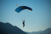 'A skydiver floats with a parachute against a blue sky and the swiss alps; Locarno, Ticino, Switzerland'