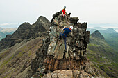 'Climber with rope on descending part of the ridge below Bruach na Frithe in the Black Cuillin; Isle of Skye, Scotland'