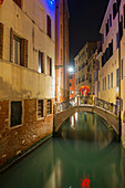 'A tranquil canal between buildings with a heart shape on a footbridge; Venice, Veneto, Italy'