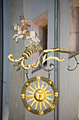 'Close up of gold sign with a sun, horn, and person on a horse; Rattenberg, Austria'