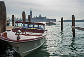 'Motorboats in the Grand Canal with buildings along the shoreline in the distance; Venice, Veneto, Italy'