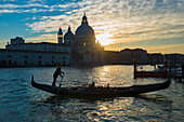 'Silhouette of a gondolier rowing his gondola with Salute church along the shoreline in the distance at sunset; Venice, Veneto, Italy'
