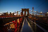 'Pedestrian path on Brooklyn Bridge heading into Manhattan at night; New York City, New York, United States of America'