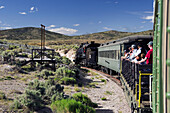 'Nevada Northern Railway train takes passengers on flat car into the hills; Ely, Nevada, United States of America'