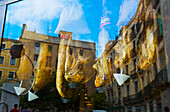 'Reflection of buildings in a window with meat hanging for sale; Barcelona, Spain'