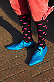 'Bright blue pointed toed shoes, heart socks and short pants, Portobello Road Market; London, England'
