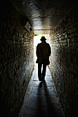 'Silhouette of a man in a top hat walking down a dark, narrow corridor; London, England'