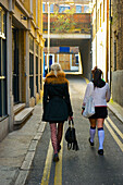 'Two young women walking down a narrow street between buildings, Brick Lane; London, England'