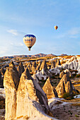 'Hot air balloons over the fairy chimneys and rugged landscape; Goreme, Cappadocia, Turkey'
